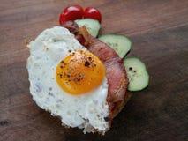 Stekt ägg med svartpeppar på en skiva av bröd Arkivfoton