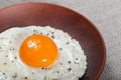Stekt ägg och bacon på en leraplatta arkivfoton