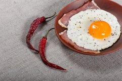 Stekt ägg och bacon på en leraplatta arkivfoto