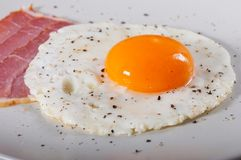 Stekt ägg och bacon på en ljus platta royaltyfria foton