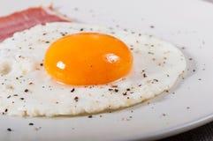 Stekt ägg och bacon på en ljus platta royaltyfria bilder