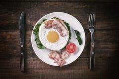 Stekt ägg och bacon på plattan arkivfoton