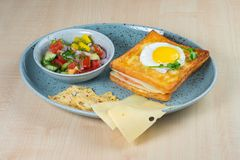 Stekt ägg och skinksmörgås, tomat, gurka och pepparsallad och ost på en platta arkivbild