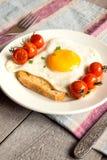 Stekt ägg på bröd med tomater Arkivbild