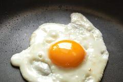 Stekt ägg på en svart panna arkivfoton