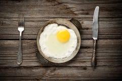 Stekt ägg på en tjänad som panna Arkivbild