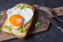Stekt ägg på ett rostat bröd med en salladslök valentin för dag s Royaltyfri Foto