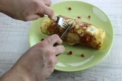 Stekt äggomelett för morgon som frukost är välfylld med zucchinin på den gröna plattan Klippa det med en kniv och en gaffel fotografering för bildbyråer