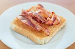 Stekt bacon på rostat bröd Fotografering för Bildbyråer