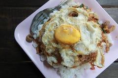 Stekt basilikablad med fega och stekte ägg på ris i träb Arkivfoto