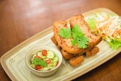 Stekt bröd med finhackad grisköttspridning på trätabellen Fotografering för Bildbyråer