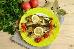 Stekt fisk & x28; carp& x29; på steknålar med styckspansk peppar, sol-torkade tomater och citronen Royaltyfri Fotografi