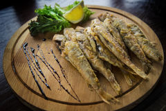 Stekt fisk för röd multefiskar på en träplatta med citronen och sallad royaltyfri fotografi