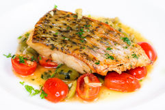 Stekt fisk med grillade körsbärsröda tomater Royaltyfria Bilder