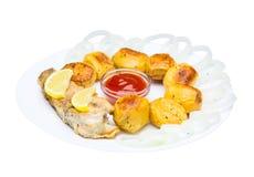 Stekt fisk med potatisar och högg av lökar med ketchup Isolat Arkivbild