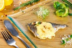 Stekt fisk med sås på den glass plattan, bästa sikt Grillad fisk som tjänas som med sås och grönska arkivbilder