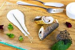 Stekt fisk med sås på den glass plattan Grillad fiskrulle som tjänas som med grönska fotografering för bildbyråer