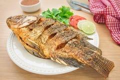 Stekt fisk på den vit plattan och doppsås royaltyfri foto