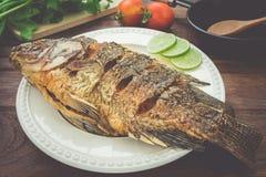Stekt fisk på plattan med grönsaker och pannan, filtrerad bild Arkivfoto
