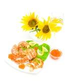 Stekt fisk, räka och kaviar, ett exponeringsglas av vin och solrosor på Royaltyfria Foton