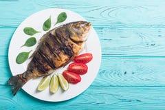 Stekt fiskdorado med limefrukt, tomater och spenat royaltyfria bilder