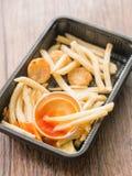 Stekt franska och ketchup i svart bunke på trätabellen Royaltyfri Bild
