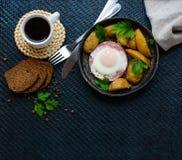 Stekt ägg i salami och bakade potatisar Undergivenhet av en stekpanna med ett kopp kaffe- och rågbröd frukost Arkivbilder