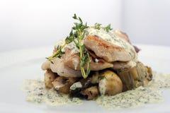 Stekt griskött med champinjoner, potatisar, rosmarin och tartarsås på en vit bakgrund royaltyfri bild