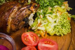 Stekt grisköttbentrumpinne, knä av en vildsvin med grönsaker av röda och gula tomater, vitlök, persilja och basilika och arkivfoton