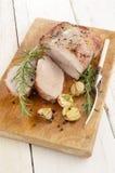 Stekt grisköttstek på ett träbräde Fotografering för Bildbyråer