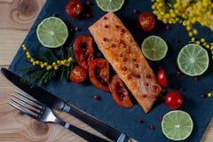 Stekt havsfisk med stycken av en tomat och en limefrukt royaltyfria foton