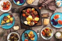 Stekt kött med grönsaker i en panna, en sallad och mellanmål Royaltyfri Foto