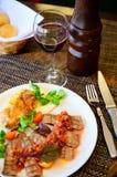 Stekt kött med grönsaker och sås på en platta royaltyfri fotografi