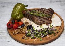 Stekt kött med tomater, vitlök, söt peppar, brun trästa royaltyfri bild