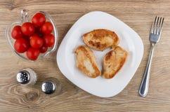 Stekt kalkonkött i platta, salt, peppar, tomater och gaffel Arkivfoton