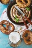 Stekt korv med öl och kringlor Arkivfoto