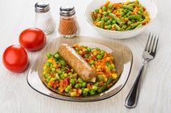 Stekt korv med grönsakblandningen, salt, peppar, tomater och för Arkivbilder