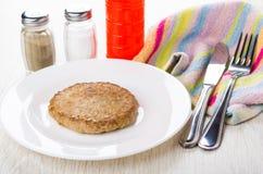 Stekt kotlett i plattan som är salt, peppar, ketchup, gaffel, kniv Arkivbilder