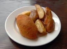 Stekt kotlett och bakad potatis Royaltyfri Foto