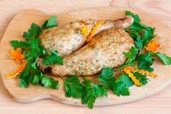 Stekt kyckling lägger benen på ryggen med parsley på stiga ombord fotografering för bildbyråer