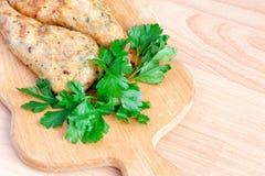 Stekt kyckling lägger benen på ryggen med parsley på stiga ombord royaltyfria bilder