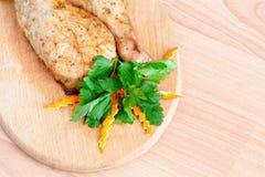Stekt kyckling lägger benen på ryggen med parsley på stiga ombord royaltyfri foto
