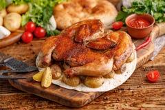 Stekt kyckling med garnering av bakade unga potatisar med utsökta anordningar Stilleben på en träbakgrund Royaltyfria Foton