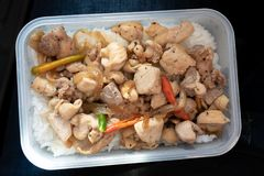 Stekt kyckling med lever, bönor och chili på ris i ask royaltyfria foton