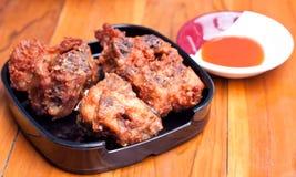 Stekt kyckling med sås på trä bordlägger Royaltyfria Foton