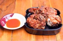 Stekt kyckling med sås på trä bordlägger Royaltyfria Bilder