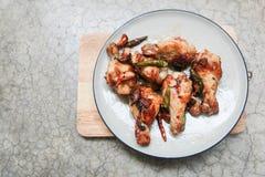 stekt kyckling med vitlök och chili i maträtt på konkret backgro Arkivbild