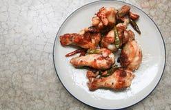 stekt kyckling med vitlök och chili i maträtt på konkret backgro Arkivbilder