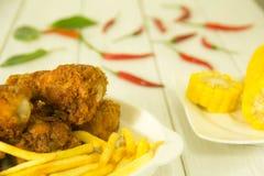 Stekt kyckling och franska småfiskar på tabellen arkivfoto