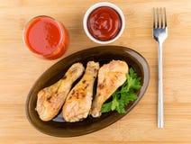 Stekt kycklingben i svart maträtt, tomatfruktsaft och sås Arkivbilder